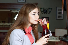 Brunette drinking from a tube juice sitting on the bar Stock Photo
