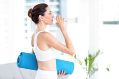 Brunette drinking water while holding exercise mat Royalty Free Stock Photography