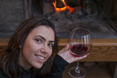 Brunette drinking wine by fireplace and looking at camera Royalty Free Stock Photos