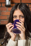 Brunette drinks tea from a mug. Screwing up your eyes Stock Photo