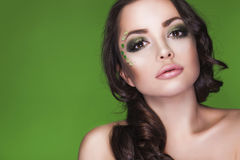 Brunette dryad woman with creative make up and beads on her face, curly hair and costume made of leaves on green backgro Royalty Free Stock Images