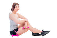 Brunette with dumbbells sitting Stock Photography