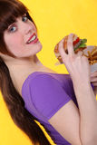 Brunette eating a burger Royalty Free Stock Photos
