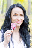 Brunette eating red candy with long hairs Royalty Free Stock Photography
