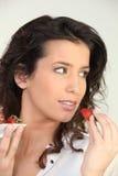 Brunette eating strawberries Stock Images