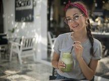 Brunette in een bandana die een goede tijdzitting in moderne exotische koffie met groene drank in haar handen hebben, het dragen stock afbeeldingen