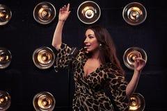 Brunette in einem sexy Leoparden beeinflussend, kleiden Sie mit den oben schauenden Händen an lizenzfreies stockbild
