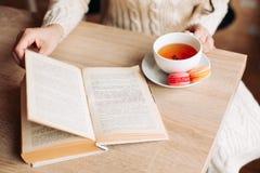 Brunette in einem trinkenden Tee des Cafés, die Bonbons essend und lesen ein Buch, gewelltes Haar Stillstehen nach einem Tag des  lizenzfreies stockbild