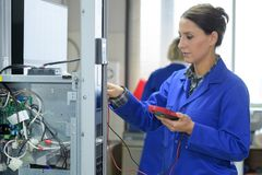 Brunette electrician holding calibrating device Royalty Free Stock Photo