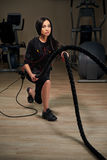 Brunette EMS fitness woman doing crossfit training using rope. G Royalty Free Stock Photo