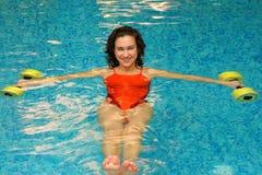 Brunette en agua con los dumbbels Imagenes de archivo