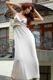 Brunette en alineada larga cerca del hotel pasado de moda Imagen de archivo