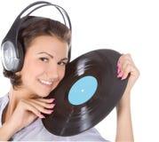 Brunette en auriculares con el expediente de vinilo imagen de archivo