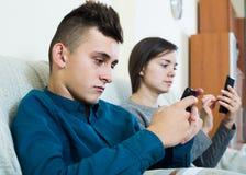 Brunette en tiener die de schermen van smartphones bekijken stock foto's