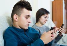 Brunette en tiener die de schermen van smartphones bekijken royalty-vrije stock foto