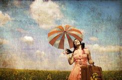 Brunette Enchantress mit Regenschirm und Koffer Stockbilder