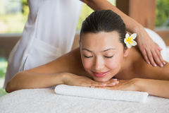 Brunette enjoying a peaceful massage with eyes closed Stock Images