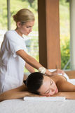 Brunette enjoying a peaceful massage with eyes closed Royalty Free Stock Photo