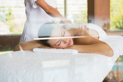 Brunette enjoying a peaceful massage with eyes closed Royalty Free Stock Images