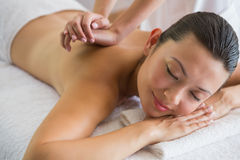 Brunette enjoying a peaceful massage with eyes closed Stock Photography
