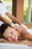 Brunette enjoying a peaceful massage smiling at camera Royalty Free Stock Photos