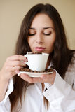Brunette enjoying smell of coffee Stock Photo