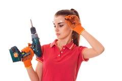 Brunette-Erbauermädchen Cutie lässt junges in der Uniform und in den Gläsern Erneuerung mit die Hände herein bohren, die auf Weiß lizenzfreie stockfotografie