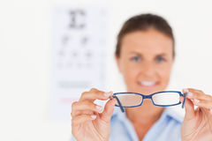 Brunette eye specialist handing out glasses Stock Photo
