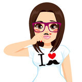 Brunette Fake Mustache Girl. Funny brunette hipster girl making faces pretending to have fake mustache in finger wearing white shirt with I love mustache print Stock Photography