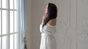 Brunette fashion model in white dress posing on camera in studio stock video footage