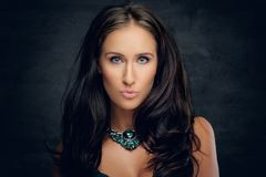 Brunette female with costly necklace. Close up studio portrait of brunette female with costly necklace stock image