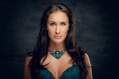 Brunette female with costly necklace. Close up studio portrait of brunette female with costly necklace royalty free stock images