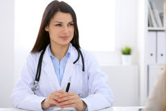 Brunette female doctor talking to patient in the hospital Stock Photo