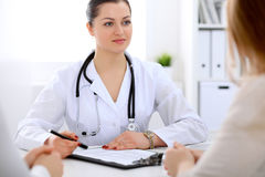Brunette female doctor talking to patient in the hospital Royalty Free Stock Photos