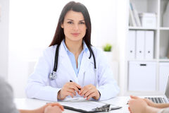 Brunette female doctor talking to patient in the hospital Stock Images