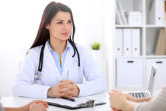 Brunette female doctor talking to patient in the hospital Stock Photography