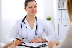 Brunette female doctor talking to patient in the hospital Stock Photos