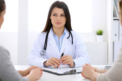 Brunette female doctor talking to patient in the hospital Royalty Free Stock Images