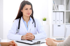 Brunette female doctor talking to patient in the hospital Royalty Free Stock Photo