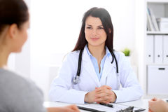 Brunette female doctor talking to patient in the hospital Stock Image
