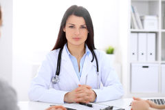 Brunette female doctor talking to patient in the hospital Royalty Free Stock Image