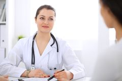 Brunette female doctor talking to patient at hospital office. Physician says about medical exams results for choosing. Optimal treatment. Healthcare and Royalty Free Stock Photography