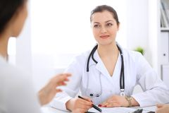 Brunette female doctor talking to patient at hospital office. Physician says about medical exams results for choosing. Optimal treatment. Healthcare and Royalty Free Stock Photo