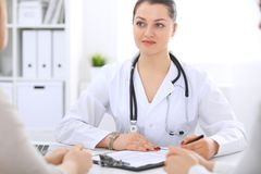Brunette female doctor talking to patient at hospital office. Physician says about medical exams results for choosing. Optimal treatment. Healthcare and Royalty Free Stock Image