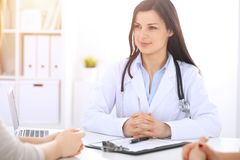 Brunette female doctor talking to patient at hospital office. Physician says about medical exams results for choosing. Optimal treatment. Healthcare and royalty free stock photos