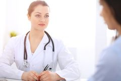 Brunette female doctor talking to patient at hospital office. Physician says about medical exams results for choosing. Optimal treatment. Healthcare and royalty free stock images