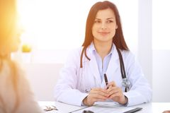 Brunette female doctor talking to patient at hospital office. Physician says about medical exams results for choosing stock image
