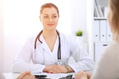 Brunette female doctor talking to patient at hospital office. Physician says about medical exams results for choosing. Optimal treatment. Healthcare and stock photography