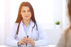 Brunette female doctor talking to patient at hospital office. Physician says about medical exams results for choosing. Optimal treatment. Healthcare and stock image