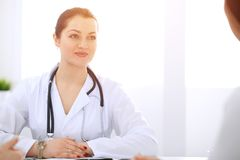 Brunette female doctor talking to patient at hospital office. Physician says about medical exams results for choosing. Optimal treatment. Healthcare and stock images